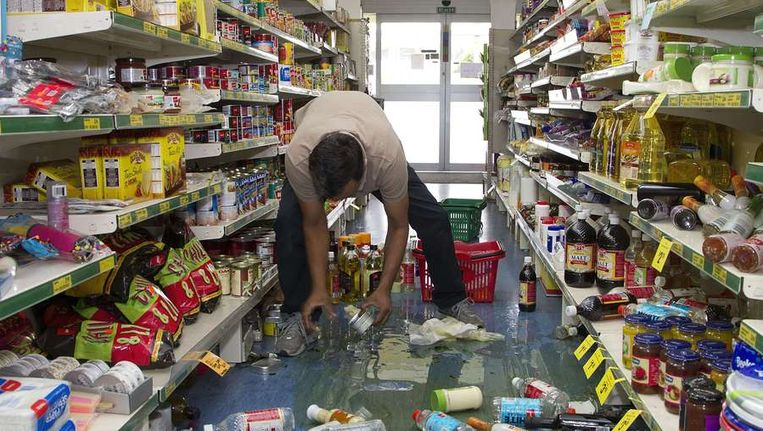 Een winkeleigenaar ruimt producten op na de aardbeving in Eketathuna in de regio Wairarapa. Beeld afp