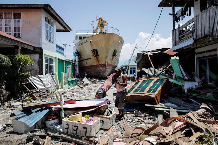 Een man draagt zijn bezittingen weg in Wani, Donggala, in het midden van Sulawesi, na de zware aardbeving en tsunami eind september, waarbij duizenden mensen om het leven kwamen.