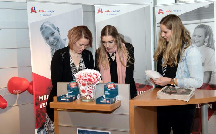 HARDENBERG -  Brenda Stoeten (l) medewerkster communicatie en voorlichting van het Alfa college richt met de stagiaires Merlijn de Witte (m) en Isabel Nijkamp de ontvangstbalie van de zorg popup-winkel in Hardenberg  in.