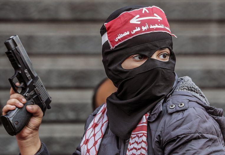 Een Palestijnse jongen houdt een wapen vast tijdens een bijeenkomst van het Volksfront voor de Bevrijding van Palestina (PFLP) in december 2019. Beeld Hollandse Hoogte / EPA