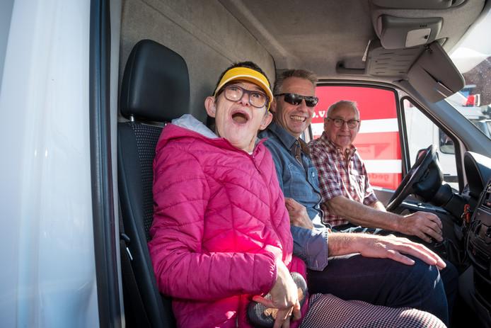 Hennie Wittingen geniet met volle teugen. Ze zit met haar broer en begeleider Bert Wittingen in de vrachtwagen van chauffeur Jan de Graaf.