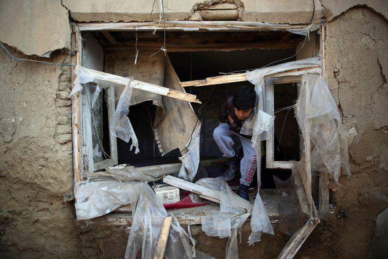 Een Afghaans jongetje bij zijn huis, dat beschadigd raakte bij een aanslag in december nabij luchtmachtsbasis Bagram, de belangrijkste Amerikaanse basis ten noorden van de hoofdstad Kabul.   Beeld AP