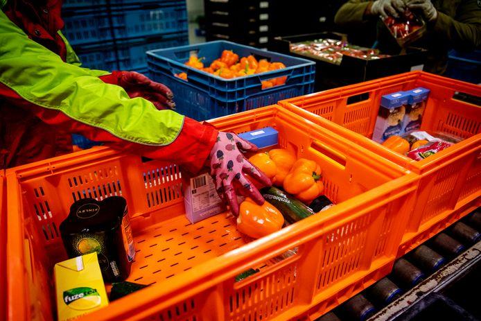 Een medewerker van de voedselbank vult een krat met eten.