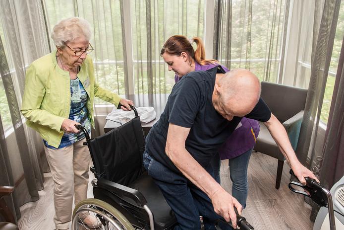 De 90-jarige mevrouw graumans (links) is nog altijd actief als vrijwilligster bij Thebe Lucia. ze haalt haar vaste cliënt op en brengt hem in de rolstoel naar de kerkdienst.