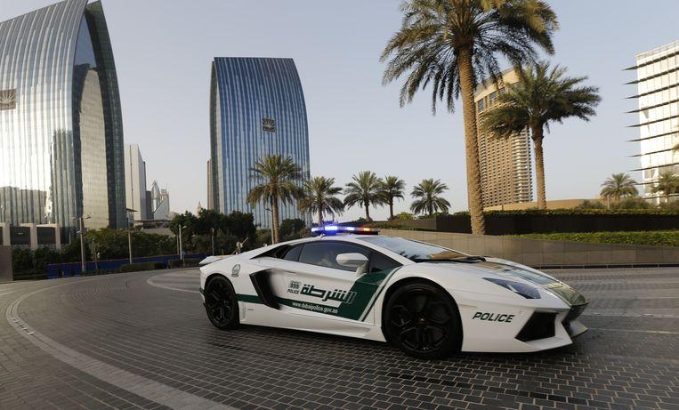 Politie-agenten in Dubai patrouilleren in een Lamborghini. Beeld AFP