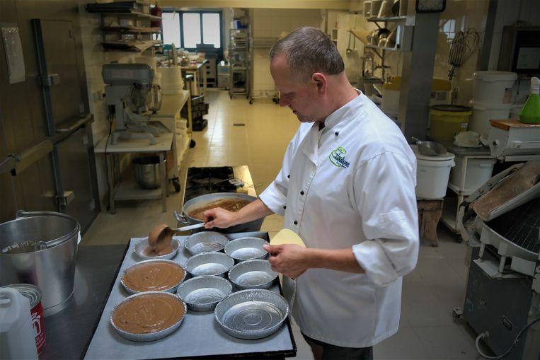 De bakker doet het deeg in de taartvormen.