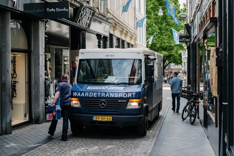 Een geldloper van SecurCash haalt geld op bij winkels in Maastricht. Beeld Hollandse Hoogte / Erik van 't Woud