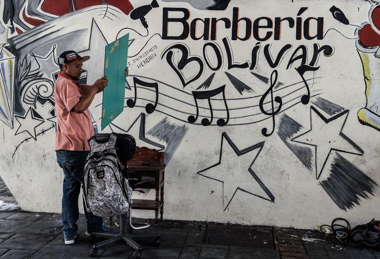Een kapper biedt zijn diensten aan onder een brug in Caracas, mei 2018. De lagere prijzen van dit soort onder bruggen of open markten aangeboden diensten zijn lager en daarom aantrekkelijk voor mensen die zich een bezoek aan de kapsalon niet kunnen veroorloven.  Beeld AFP