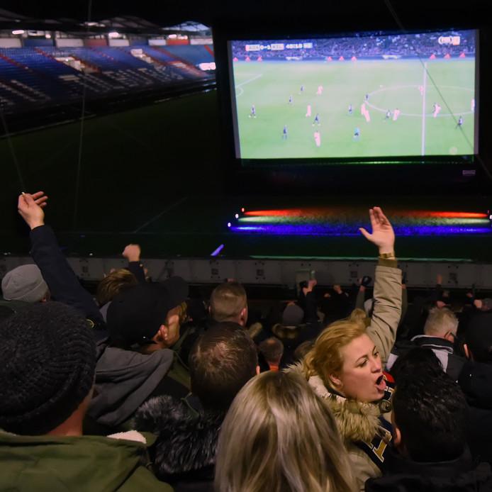 Supporters van Willem II juichen om de overwinning van hun club op Ajax. Ze keken naar de wedstrijd Ajax-Willem II in hun eigen stadion.