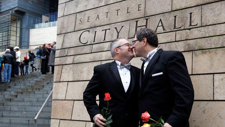 Een Amerikaans echtpaar kust elkaar na in het stadhuis van Seattle in de echt te zijn verbonden, zondag 9 december. Beeld AP