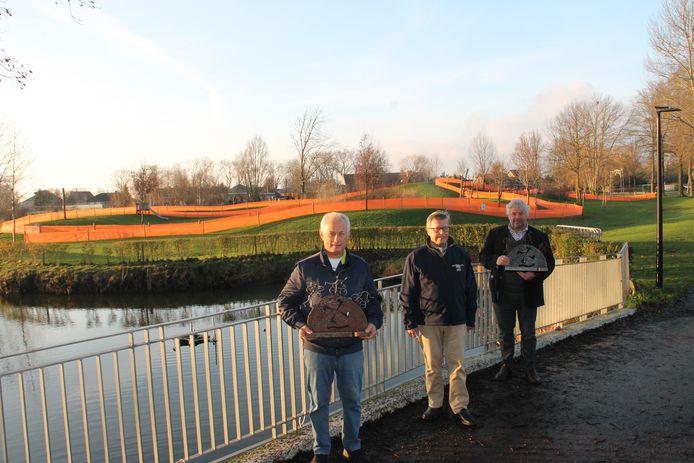 Parcoursbouwers Hubert Debacker en Pierre Buyse pronken samen met kunstenaar Marc Vanhecke met de trofeeën die de winnaar bij de dames en heren krijgen. Op de achtergrond ligt het BK-parcours.