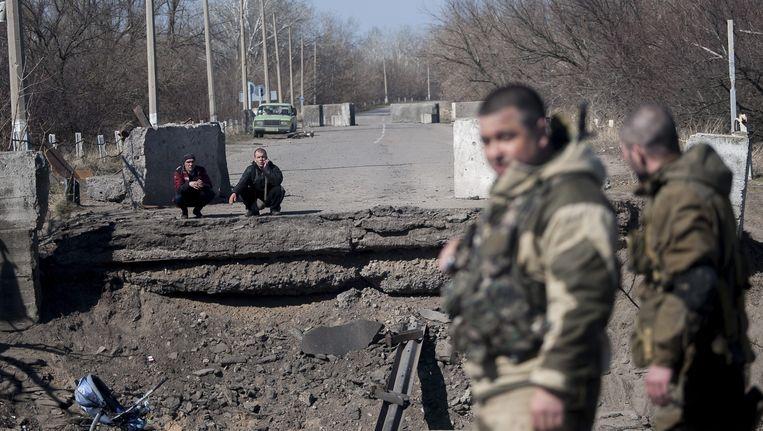 Pro-Russische seperatisten staan bij een kapotte brug in de buurt van Loehansk. Beeld epa