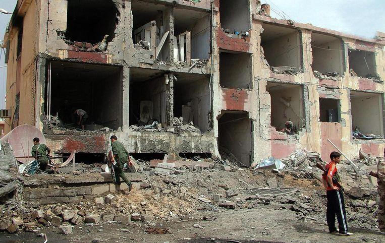Syrische politiemannen bij verwoeste gebouwen in Deir Al-Zour in 2012. Beeld null