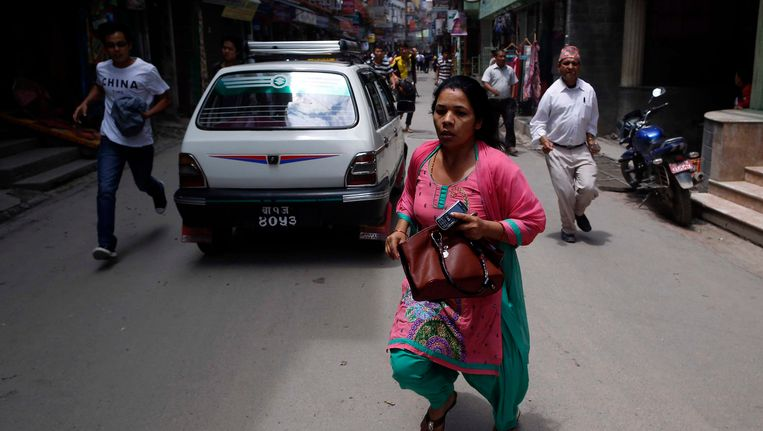 Inwoners van Kathmandu rennen in paniek de straat op. Beeld epa