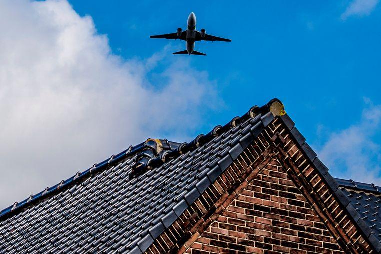 Een vliegtuig scheert laag over de huizen bij Schiphol. Beeld Hollandse Hoogte /  ANP