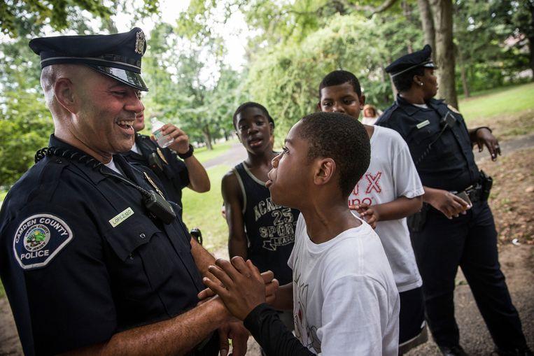 Politieman Jim Lopez maakt een geintje met Omar Headen tijdens een park-opruimdag in Camden. Beeld null