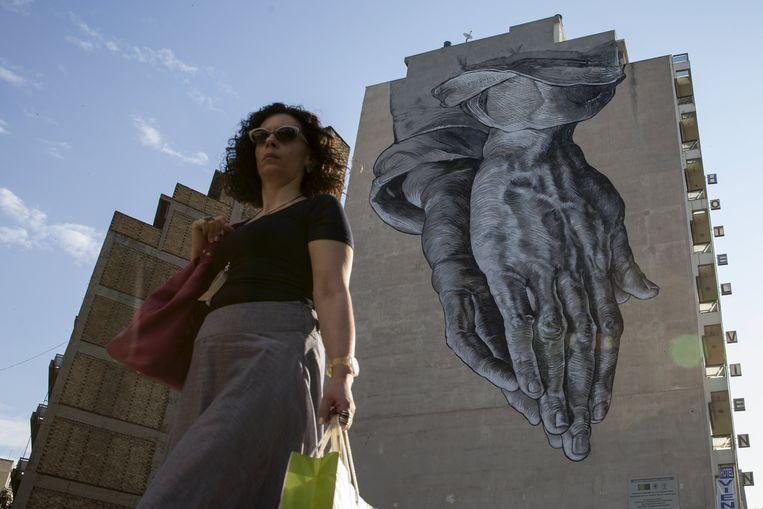Een Griekse vrouw loopt langs een monument met biddende handen in Athene. Beeld reuters