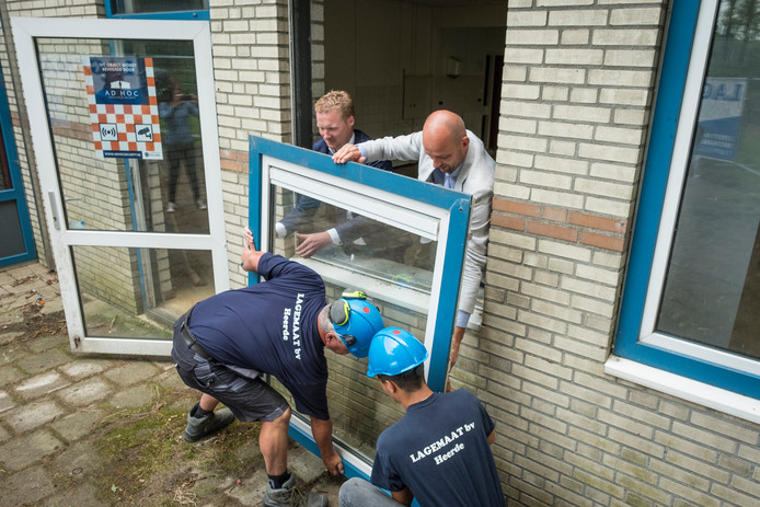 Gerd-Jan Jongerman (linksachter) en Auke Schipper rechtsachter maken met hulp van twee Lagemaat-medewerkers het eerste van tientallen raamkozijnen los.
