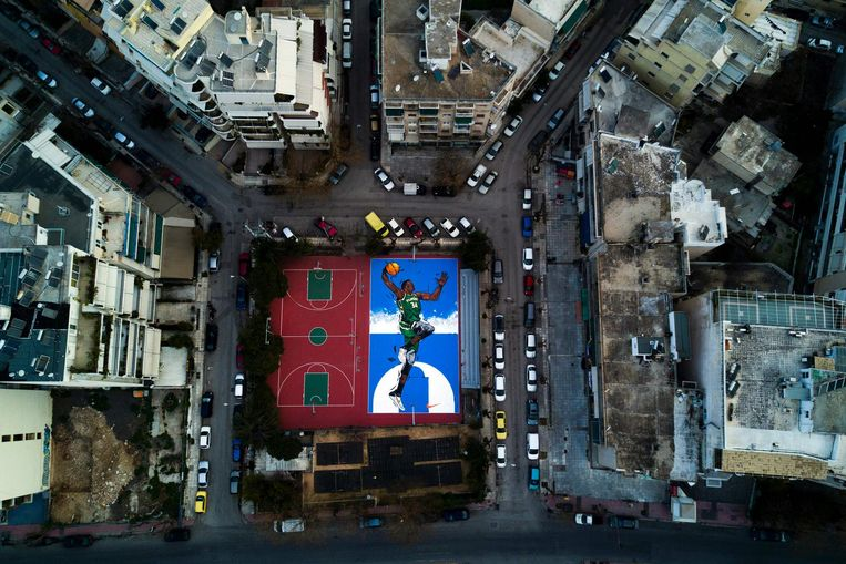 Op jonge leeftijd sportte 'The Greek Freak' op de pleintjes in Athene. Meestal voetballen, totdat zijn grote basketbaltalent werd ontdekt. Nu ruim tien jaar later staat midden in Athene deze grondschildering op een pleintje in zijn oude buurt. Beeld afp