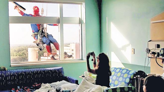 Kinderen in All Children's Hospital in St. Petersburg in Florida kijken hun ogen uit en maken een foto van Spider-Man.