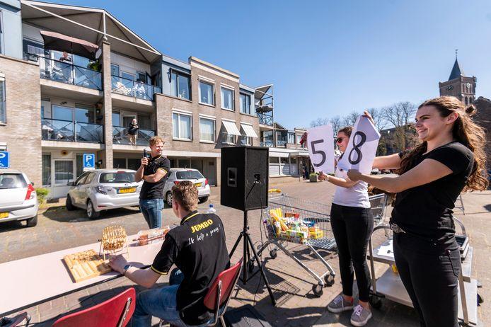 Lynn en Fenne (rechts) houden de cijfers omhoog voor de deelnemers aan de balkonbingo in Schaijk. Niek roept de nummers om.