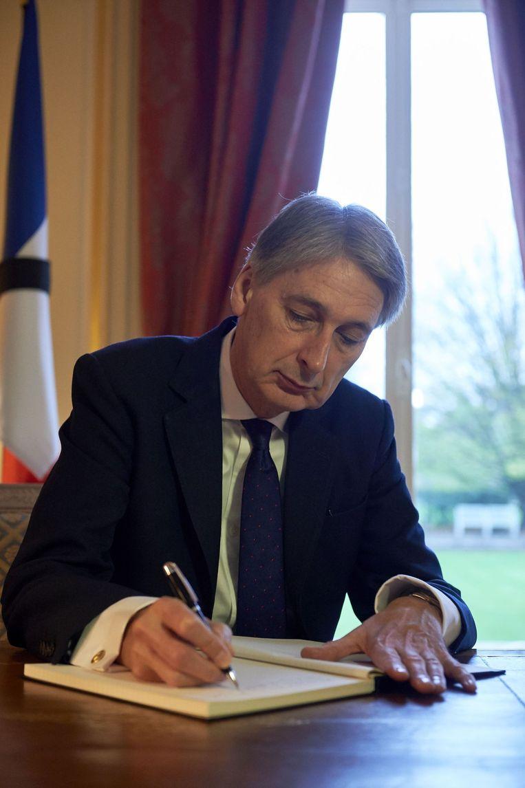 Philip Hammond tekende eerder deze week het condoleanceregister voor de slachtoffers in Parijs. Beeld afp