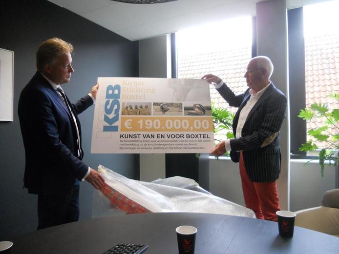 Mark Buijs en Gerard Schraverus van de kunststichting geeft een cheque terug aan de gemeente.