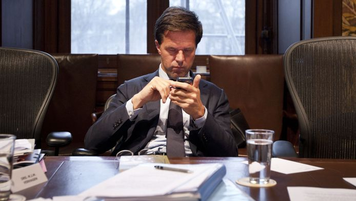 Premier Rutte bladert in zijn telefoon.