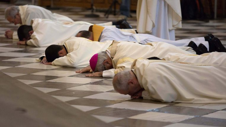 De aartsbisschop van Granada Francisco Javier Martinez en enkele priesters liggen voor het altaar om vergiffenis te vragen voor de vele gevallen van kindermisbruik in de Rooms-katholieke Kerk. Beeld reuters