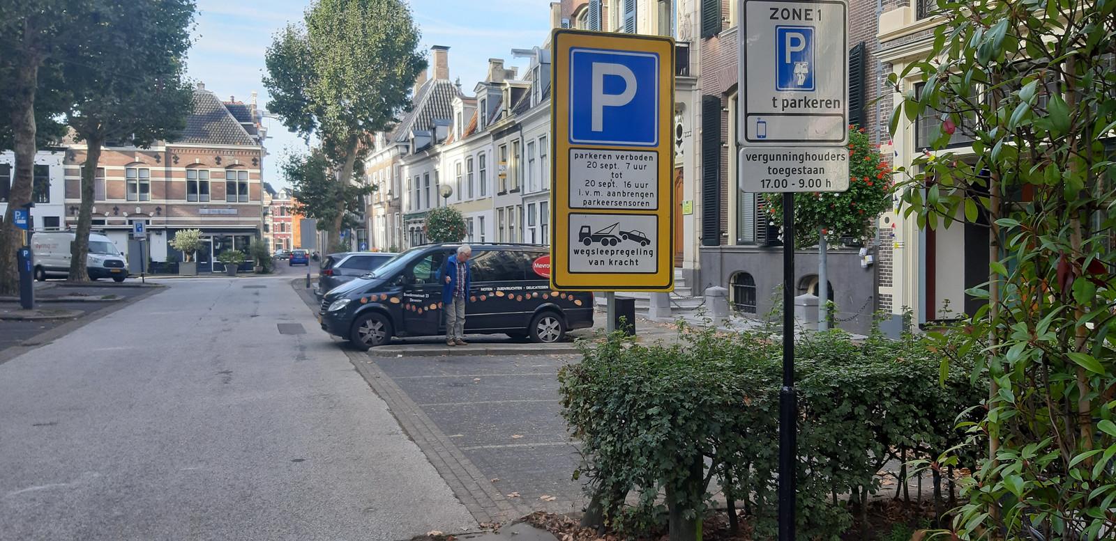 Een parkeerder kijkt verbaasd naar de sensoren die zijn aangebracht in de parkeervakken.