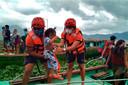 Leden van de Filipijnse kustwacht dragen een kind aan boord van een boot waarmee inwoners van de provincie Camarines Sur naar veiligere oorden worden gebracht.