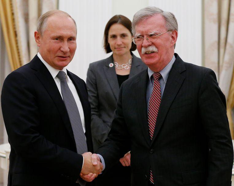 De Russische president Vladimir Poetin en de nationaal veiligheidsadviseur van president Trump, John Bolton, schudden de hand tijdens hun ontmoeting in het Kremlin, dinsdag 23 oktober, twee dagen nadat Trump dreigde om het belangrijkste ontwapeningsverdrag op te zeggen. Beeld AP