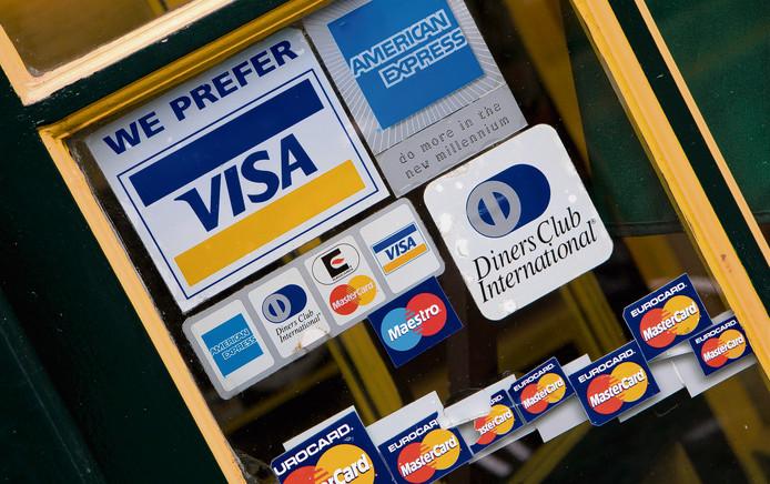 Stickers van creditcards op het raam van een horecagelegenheid in Amsterdam.