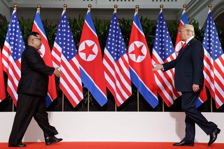 De twee leiders lopen op elkaar af voor hun eerste historische handdruk.