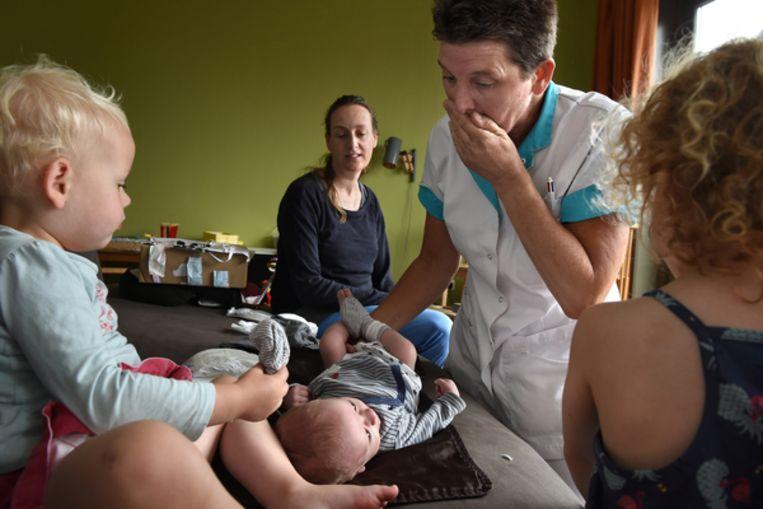Kraamverzorgende Margreet Heijkoop verschoont de vier weken oude Isak terwijl moeder Catharina en haar twee andere kinderen toekijken. Beeld Marcel van de Bergh