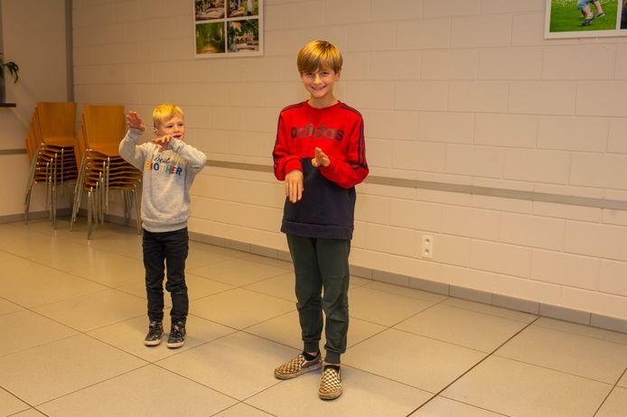 De 6-jarige Wout uit Wuustwezel, die doof geboren werd, doet samen met zijn 10-jarige buurjongen het gebaar voor 'steppen' op de eerste les Vlaamse Gebarentaal voor de tweede groep.