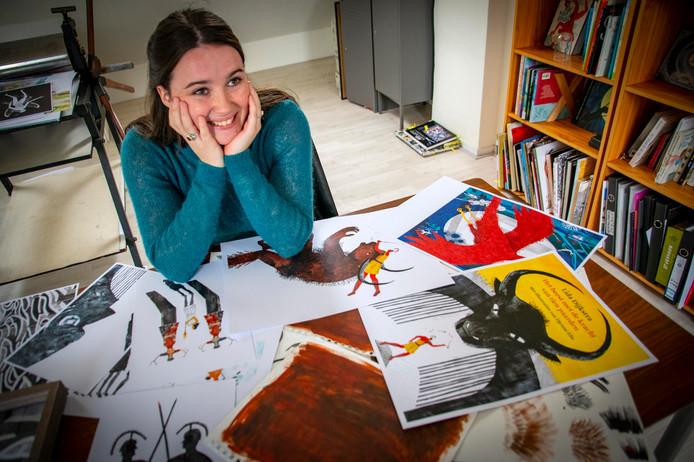 Djenné Fila in haar atelier, op tafel ligt de cover van haar debuutboek.
