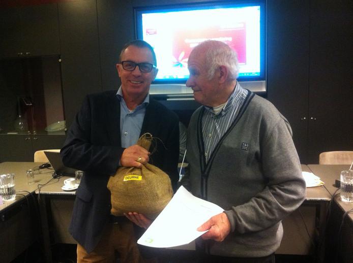 Evert van Kampen (rechts) overhandigt een zak Deurnese grond aan wethouder Helm Verhees.