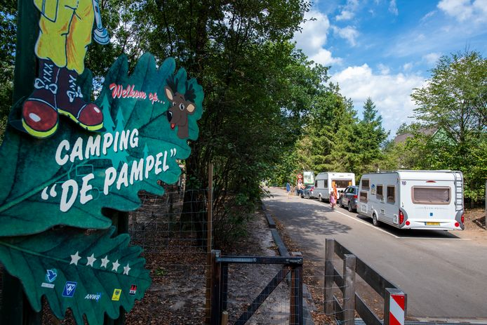 Kampeerders met caravans staan te wachten om in te checken bij camping de Pampel in Hoenderloo. Na een teleurstellend voorjaar draaien de campings een topzomer.