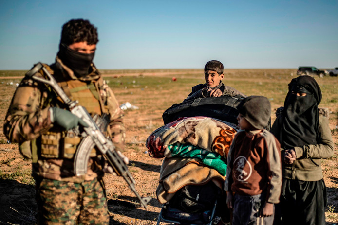 Koerdische strijders van SDF controleren de laatste vluchtelingen uit Baghouz.
