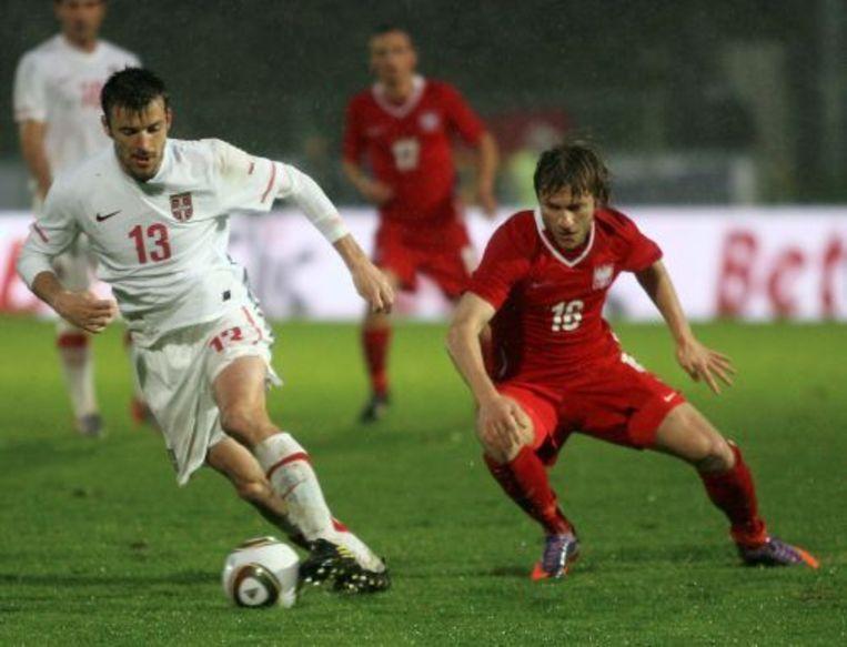 Jakub Blaszczykowski (R) van Polen en Aleksander Lukovic (L) van Servië vechten om de bal. ANP Beeld