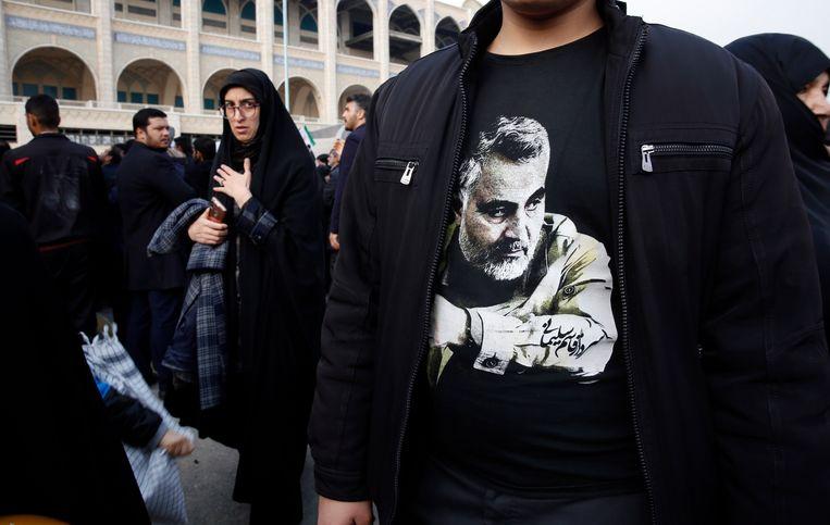 Een man draagt een T-shirt met de afbeelding van generaal Qassem Soleimani tijdens een protest tegen de Verenigde Staten in de Iraanse hoofdstad Teheran. Beeld EPA
