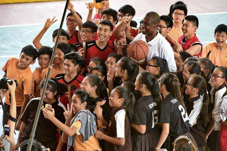 De Congolees-Amerikaanse ex-NBA-speler Dikembe Mutombo poseert met Singaporese schoolkinderen na een sportcursus. Beeld afp