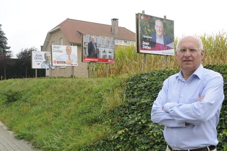 Jean Defau aan zijn vier verschillende verkiezingsborden.
