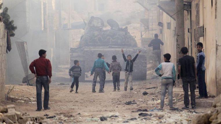 Kinderen rennen in Aleppo achter een tank aan. Beeld reuters