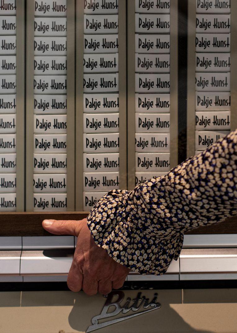 Een oude sigarettenautomaat, nu gevuld met zestig pakjes kunst. Beeld Lin Woldendorp