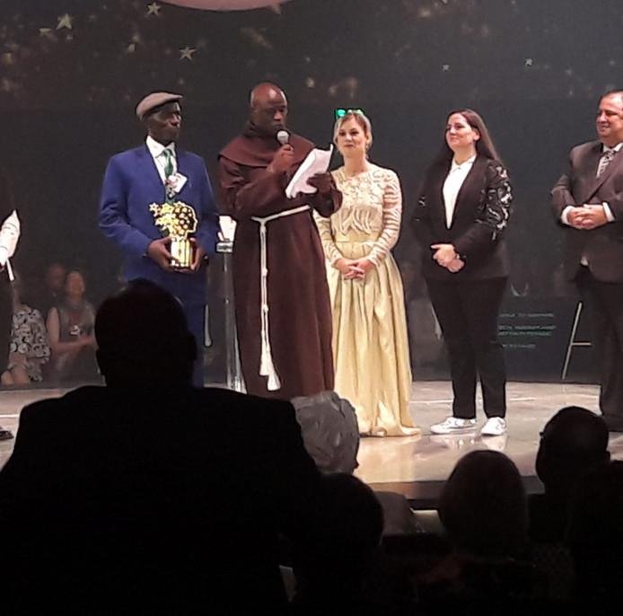 De winnaar Peter Tabichi geeft een speech, rechts naast hem staat Daisy.