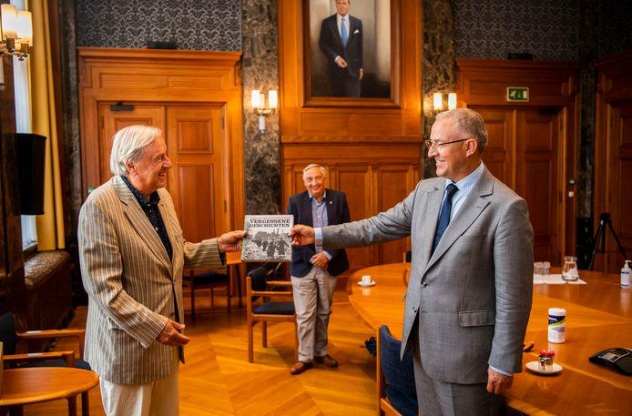 Ries Jansen (links) biedt de Duitse vertaling van 'Vergeten verhalen' aan burgemeester Ahmed Aboutaleb aan. Op de achtergrond in het midden auteur van het boek Johan van der Hoeven.