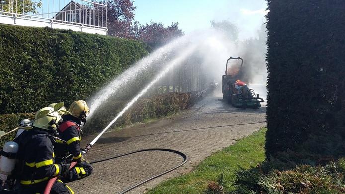 Brandweerlieden bedwingen de vlammen.