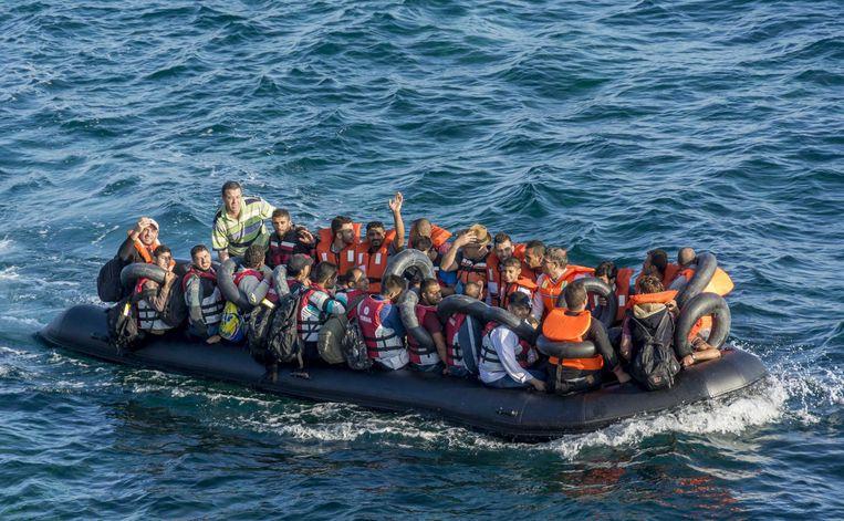Bootvluchtelingen onderweg op het water in een overvolle rubberboot Beeld anp